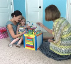 Dr. Sharon Doss works with a two-year-old and the child's mom